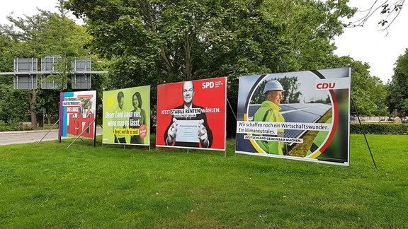 Wahlplakate von Linke, Grüne, SPD und CDU zur Bundestagswahl 2021 stehen auf einer Grünfläche am Gothaer Platz in Erfurt