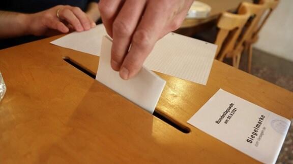 Eine Hand steckt einen Zettel in eine Wahlurne