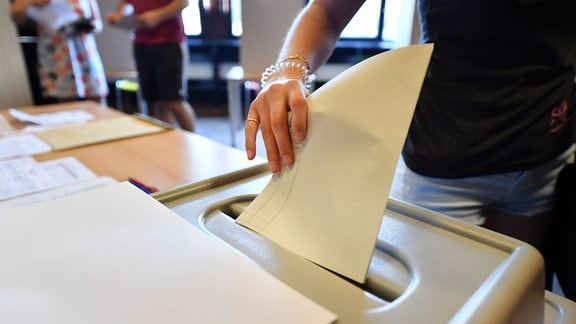Eine Wählerin wirft den Stimmzettel in die Wahlurne bei der Stimmabgabe für die Landtagswahl in einem Wahllokal.