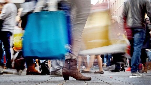 Passanten tragen ihre weihnachtlichen Einkäufe in Taschen durch die Fußgängerzone.