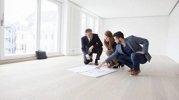 Drei Personen schauen bei Wohnungsbesichtigung auf den Grundriss der Wohnung.