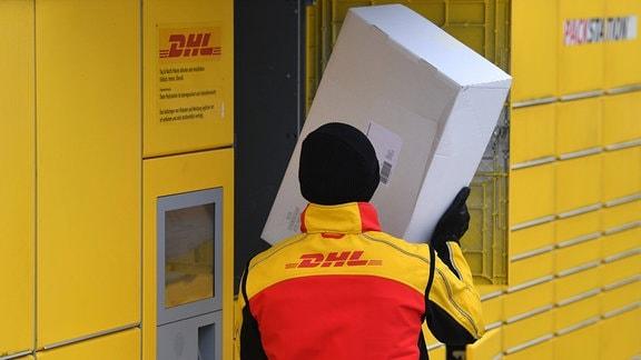 Ein DHL-Paketzsteller legt Paket in ein Fach einer Packstation.