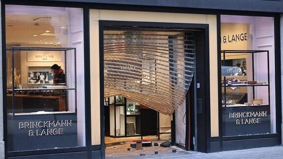 Das eingedrückte Rollgitter hängt am Eingang eines Juwelierladens herunter.