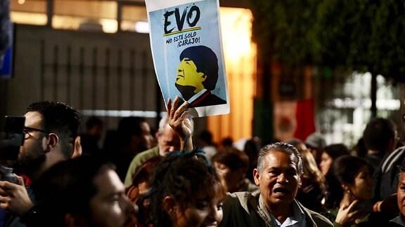 Ein Mann hält ein Plakat mit Evo Morales hoch.