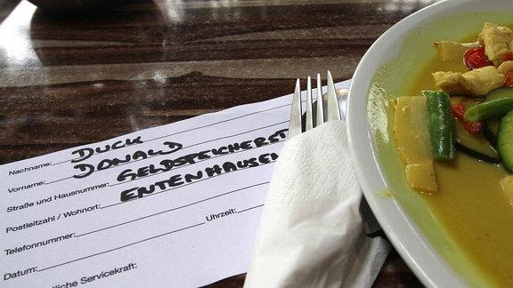 Ein mit dem offensichtlich falschen Namen Donald Duck ausgefüllter Kontaktbogen in einem Restaurant