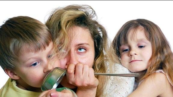 Zwei Kinder umarmen ihre Mutter, die am Rande des Nervenzusammenbruchs steht.