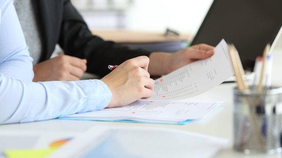 Hände von zwei Büroangestellten bei der Zusammenarbeit an einem Schreibtisch