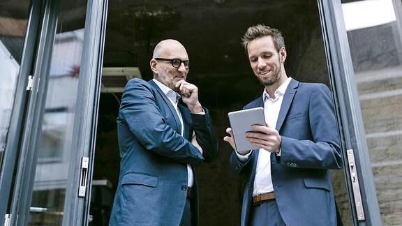 Zwei Männer stehen in einer Tür und sehen auf ein Tablet