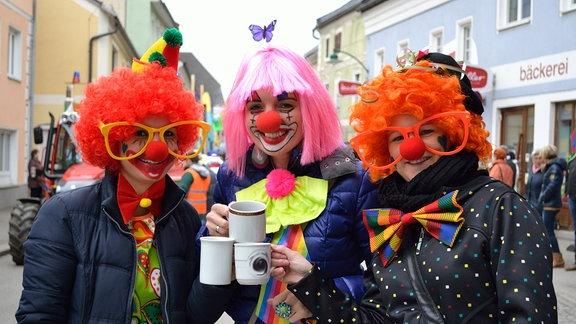 Drei Faschingsnarren stoßen mit Tassen an.