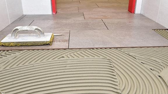 Bodenfliesen verlegen.