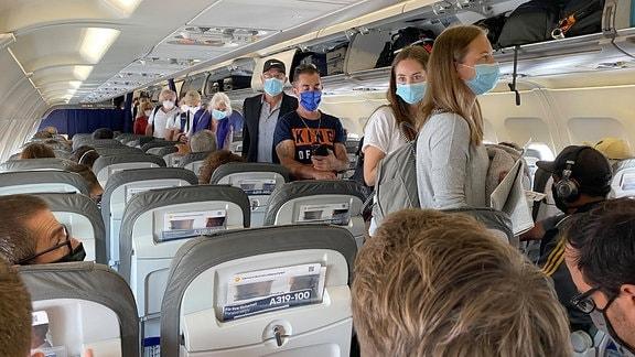 Passgiere mit Mundschutz in einem Flugzeug