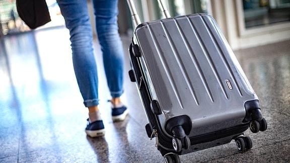 Eine Frau zieht einen Rollkoffer