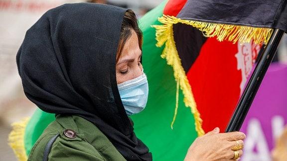 Eine Frau hält die Afghanische Fahne