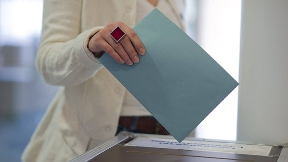 Frau bei Stimmabgabe an einer Wahlurne