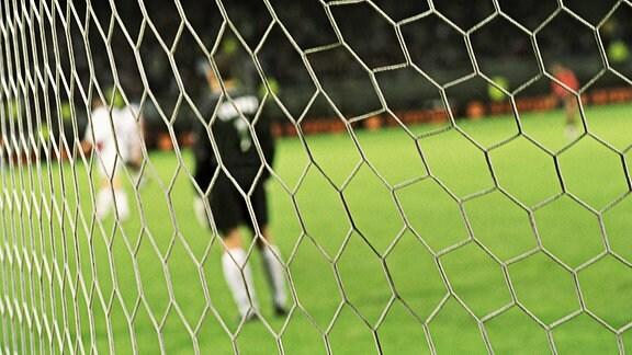 Blick durch das Netz eines Fußballtores auf ein Fußballspiel