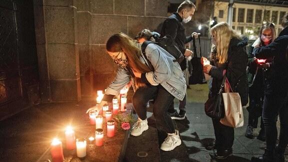 Eine junge Frau stellt bei einer Gedenkveranstaltung für das Todesopfer des Messerangriffs von Dresden eine Kerze auf
