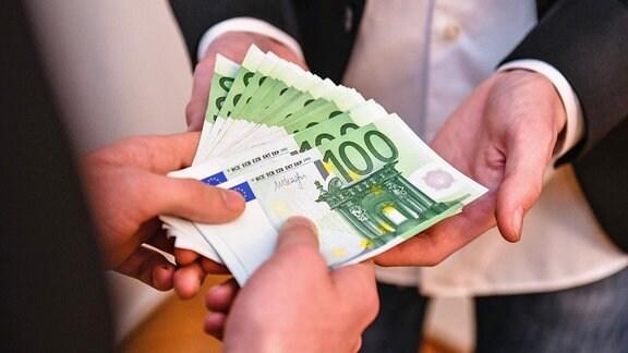Mehrere 100-Euro-Banknoten werden übergeben