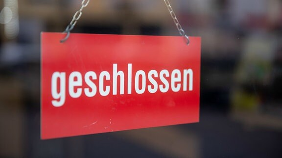 """""""Geschlossen"""" steht auf einem Schild an der Tür eines Restaurants."""
