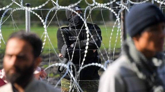 Polnischer Grenzwächter schaut auf Flüchtlingscamp hinter Grenzzaun.