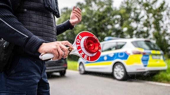Eine Polizeibeamtin steht bei einer Corona-Einreisekontrolle der Bundespolizei an der deutsch-niederländischen Grenze mit einem Polizeianhaltestab und kontrolliert Fahrzeuge im Grenzgebiet.
