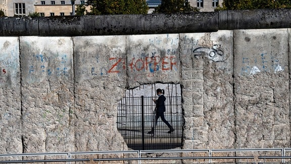 Eine Frau ist durch ein Loch der ehemaligen Grenzmauer an der Niederkirchnerstraße zu sehen.