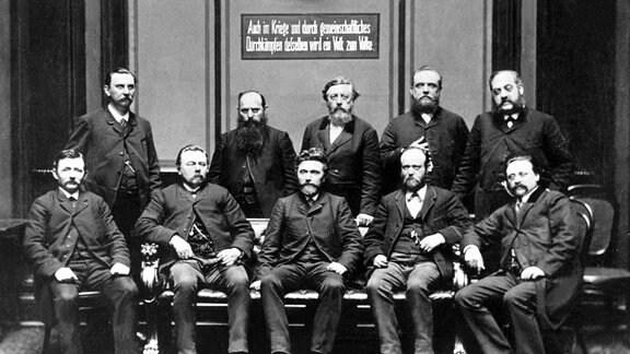 Aufnahme (ca. 1900) von führenden Mitgliedern der zur Massenbewegung aufsteigenden Sozialdemokratischen Partei Deutschland (SPD), die am 23. Mai 1863 unter dem Namen Allgemeiner Deutscher Arbeiterverein (ADAV) in Leipzig gegründet worden war. In der hinteren Reihe 3.v.l. Wilhelm Liebknecht, in der vorderen Reihe 3.v.l. August Bebel.
