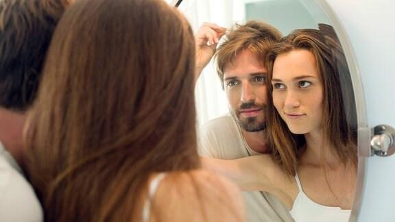 Ein Paar schauen sich ihre Haare in einem Spiegel an
