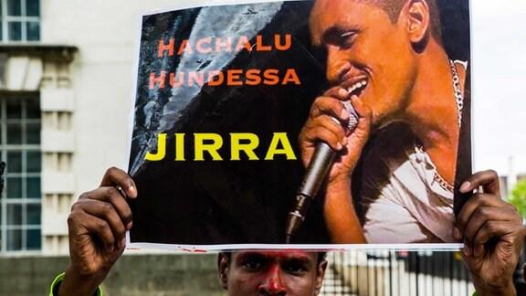 Ein Mann hält ein Bild des äthiopischen Sängers Hachalu Hundessa