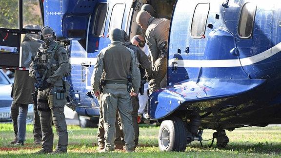 Eine Person wird von Polizisten aus einem Hubschrauber gebracht