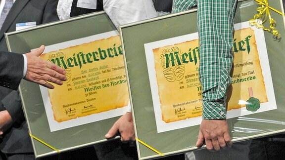 Meisterabsolventen halten bei einer Feier 2014 Meisterbriefe