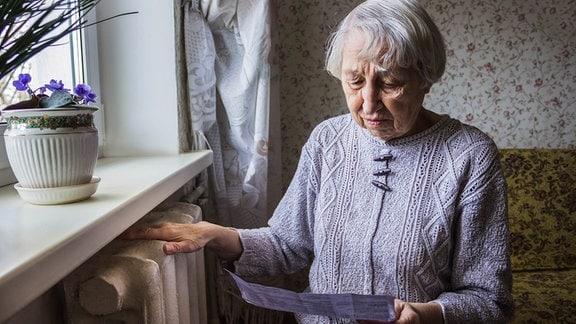 Seniorin liest eine Rechnung, während sie eine Hand auf die Heizung hält.
