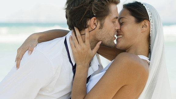Hochzeitspaar küsst sich am Strand.