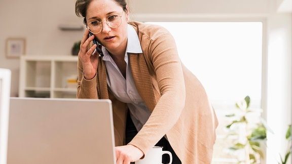 Eine Angestellte telefoniert mit dem Smartphone, während sie auf einen Laptop schaut.