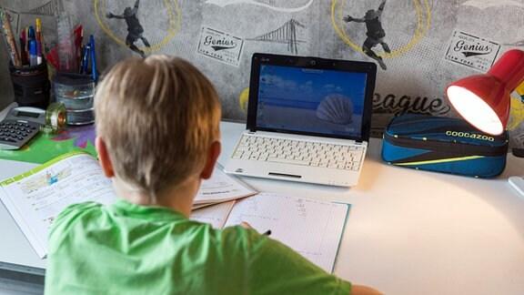 Ein Junge sitzt an seinem Schreibtisch und erledigt seine Aufgaben im Homeschooling