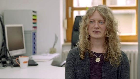 Olga Ungurs, eine Frau mit blonden langen lockigen Haaren, sitzt in ihrem Büro.