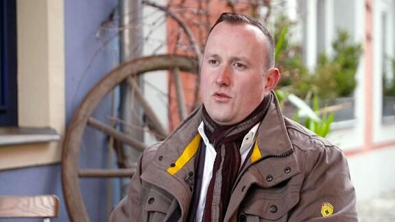 CDU-Politiker Christian Herrgott sitzt in einer grauen Jacke in einem Freisitz.
