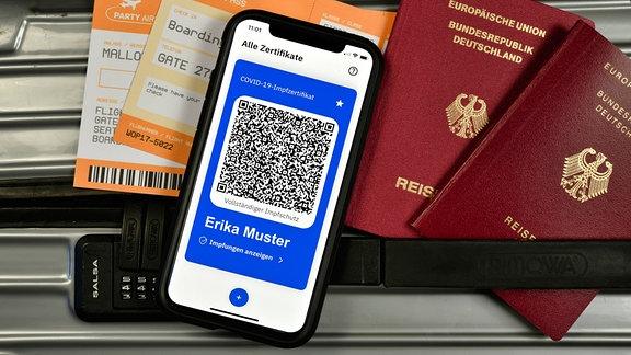 Symbolfoto Impfprivilegien, auf Koffer liegen App CovPass auf Smartphone mit digitalem europäischen Impfzertifikat inklusive QR-Code, Reisepässe, Bordkarten