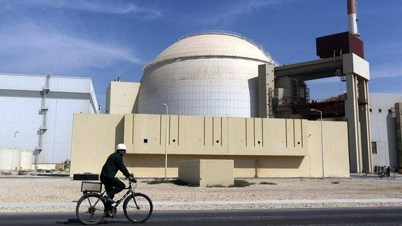 Ein Arbeiter mit einem Fahrrad vor der iranischen Atomanlage in Buschehr