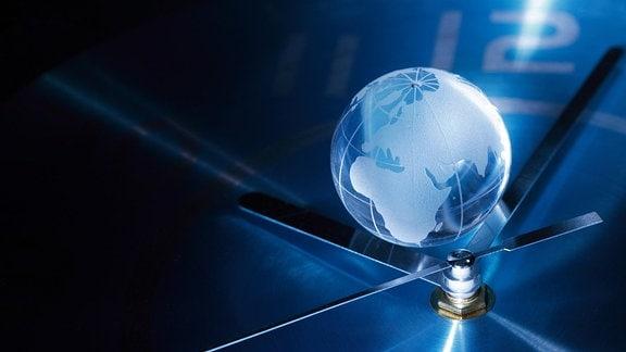 Auf dem Ziffernblatt einer Uhr liegt eine gläserne Weltkugel in der sich ein Feuerwerk spiegelt.