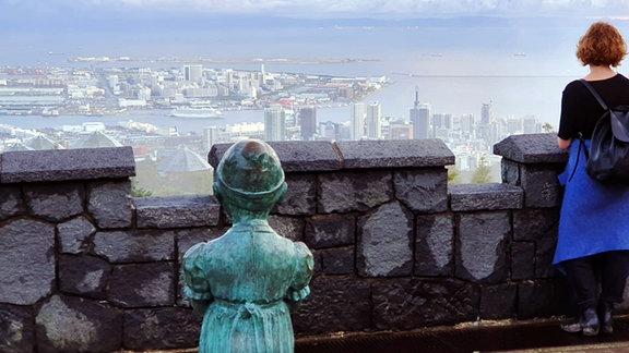 Frau steht an Mauer und schaut auf Stadt