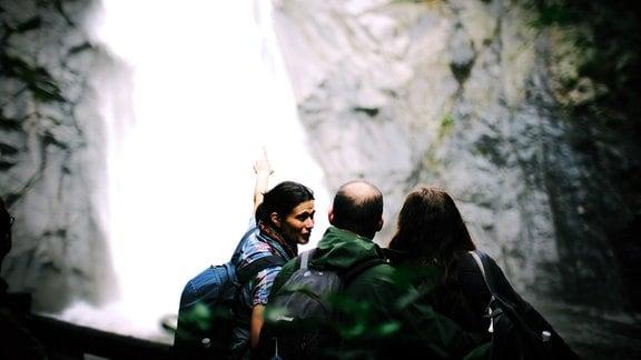 Eine Frau zeigt auf etwas, zwei Personen stehen daneben.