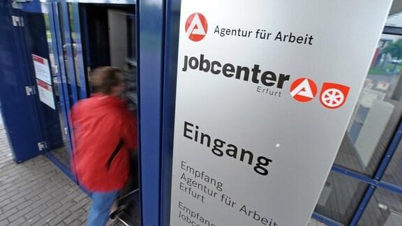 Ein Kunde geht durch die Tür eines Jobcenters.
