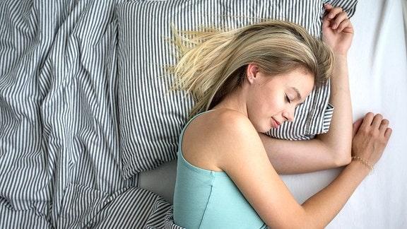 Eine junge Frau schläft in einem Bett