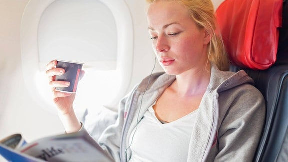 Eine junge Frau mit einem Kaffeebecher in einem Flugzeug