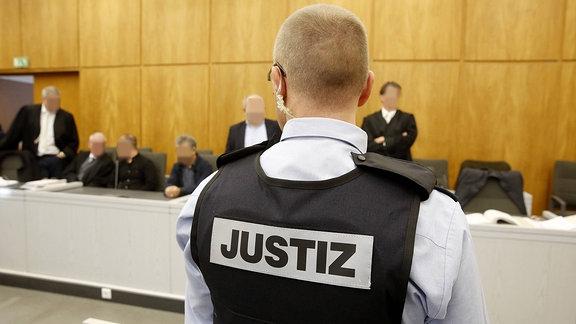 Justizbeamte bewachen Zuschauer und Angeklagte im Saal