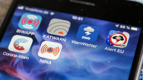 """Verschiedene Warn-Apps, darunter die Notfall-Informations- und Nachrichten-App """"Nina"""" des Bundesamts für Bevölkerungsschutz und Katastrophenhilfe, sind auf auf einem Smartphone zu sehen."""