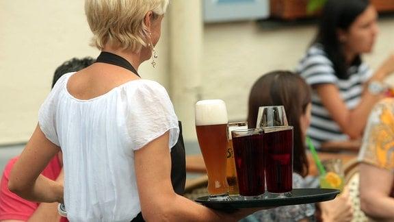 Kellnerin trägt ein Tablett mit Getränken