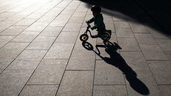 Der Schatten eines Kindes mit Laufrad