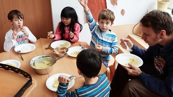Die Vorschulkinder Maximilian (5, l-r), Kisella (6) Edin (5) und Heilerzieher Oliver Mager essen am 02.11.2012 in der Kita Mucklas in Hamburg Kartoffelsuppe zu Mittag.