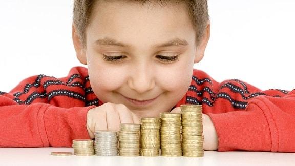 Ein Junge schaut auf einen Münzstapel vor sich